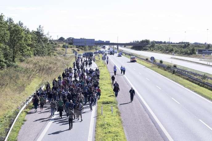 Un groupe de réfugiés escortés par la police, sur une autoroute dans le sud du Danemark le 9 septembre. En provenance d'Allemagne ils traversent le Danemark pour se rendre en Suède.