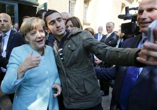 Anas Modamani prend une photo avec la chancelière Angela Merkel, en 2015. C'est cette photo qui a ensuite été détournée pour accuser M. Modamani d'être un criminel.
