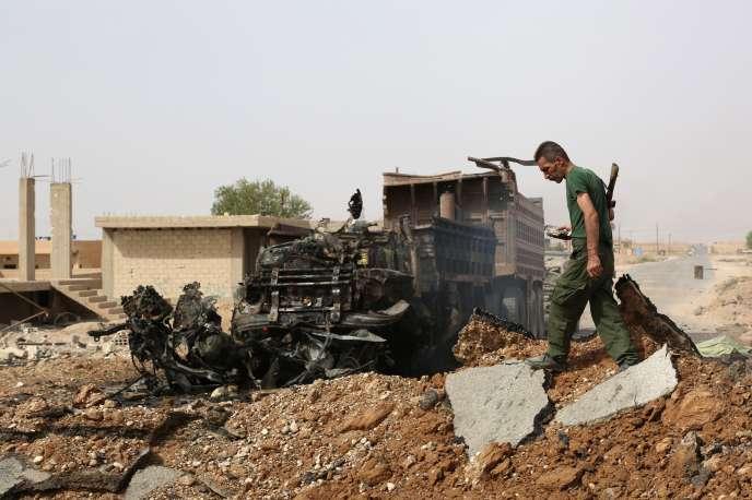Un milicien kurde inspecte le site d'un attentat contre un point de contrôle kurde, à Hassaké, dans le nord-est de la Syrie, en septembre.