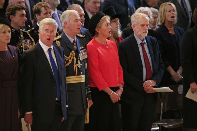 Jeremy Corbyn, en cravate rouge, garde la bouche close au milieu d'invités chantant