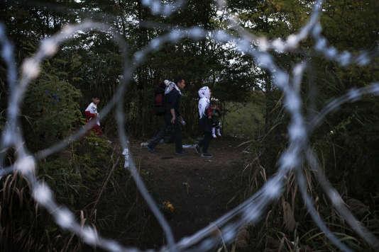 Une famille de réfugiés le long de la nouvelle clôture installée à la frontière entre la Hongrie et la Serbie, le 14 septembre.
