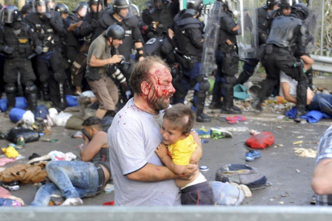 Un migrant blessé porte un enfant lors d'affrontements avec la police, mercredi 16septembre, à la frontière entre la Serbie et la Hongrie.