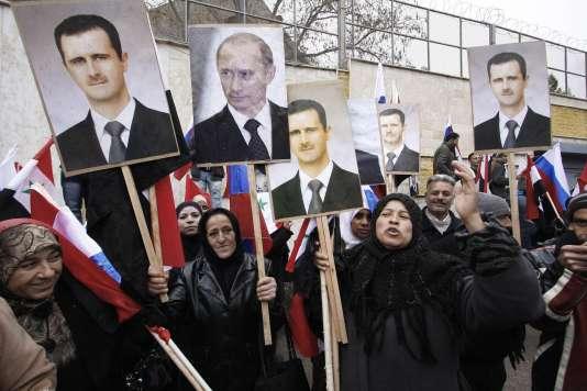Des manifestants pro-régime brandissent des photos de Vladimir Poutine et Bachar al-Assad à Damas en mars 2012.