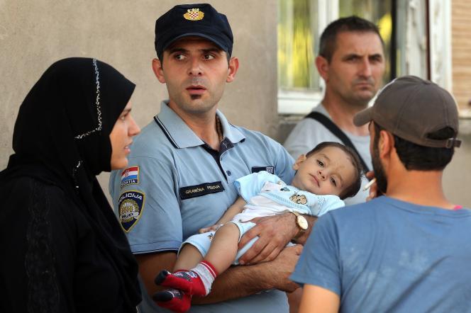 Un policier croate porte un enfant migrant à Tovarnik, près de la frontière entre la Serbie et la Croatie, le 16 septembre.