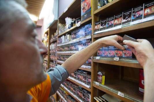Un employé d'un bureau de tabac installe des paquets de cigarettes, le 8septembre, pendant la journée de protestation contre la loi de santé.