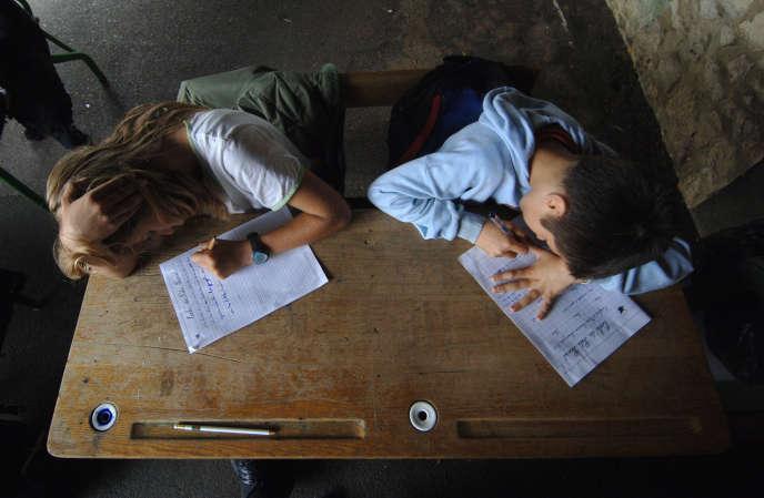 Des élèves de CM2 écrivent une dictée le 08 juin 2007 sous le préau de l'école primaire du Puits Picard, à Caen.