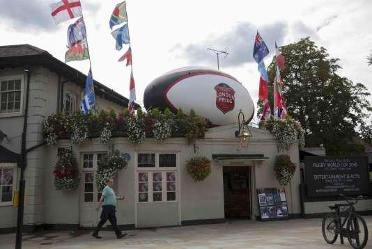 Un homme passe devant un pub surplombé d'un ballon de rugby géant, le 17septembre à Twickenham, Londres.