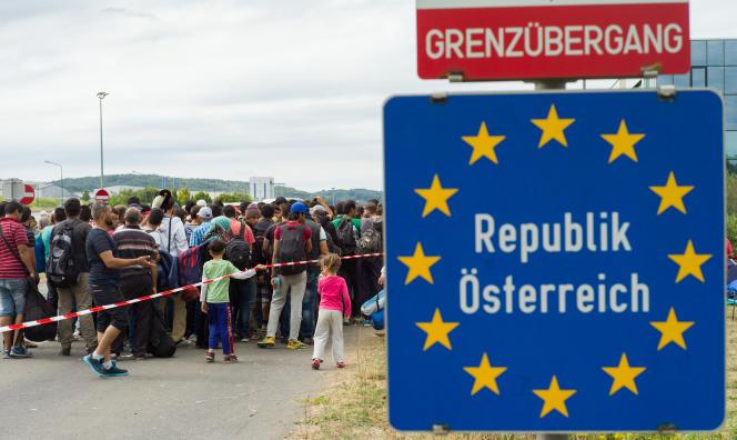 Des migrants attendent des bus après avoir franchi la frontière entre la Hongrie et l'Autriche, le 19 septembre.