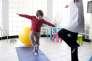 Psychomotricienne faisant des exercices de coordination et d'orientation spatiale avec une fillette de 5 ans.