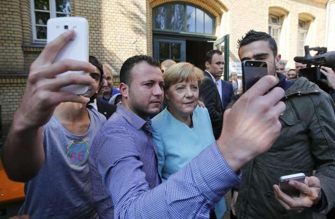 Des migrants de Syrie et d'Irak se prennent en photo aux côtés d'Angela Merkel, dans un camp de réfugiés à Berlin, le 10 septembre 2015.