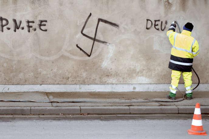 Une personne nettoie le mur extérieur du cimetière de Montigny-lès-Metz, qui a été recouvert d'inscriptions nazies et antisémites dans la nuit, le 11 février 2009.