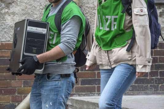 Des policiers allemands emportent avec eux un ordinateur à l'occasion de leur perquisition dans le quartier de Tempelhof-Schöneberg, mardi22septembre2015.