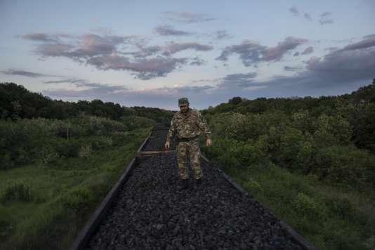 Un combattant volontaire pro-Kiev se tient sur un train transportant du charbon de la région séparatiste de Lougansk vers l'ouest, le 2 juin.