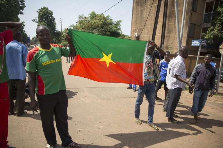 Des Burkinabè tiennent un drapeau du Burkina Faso dans les rues de Ouagadougou, en septembre 2015.