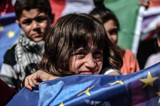 Un jeune migrant tient un drapeau de l'Union européenne dans un terminal de bus à Istanbul, le 19 septembre.