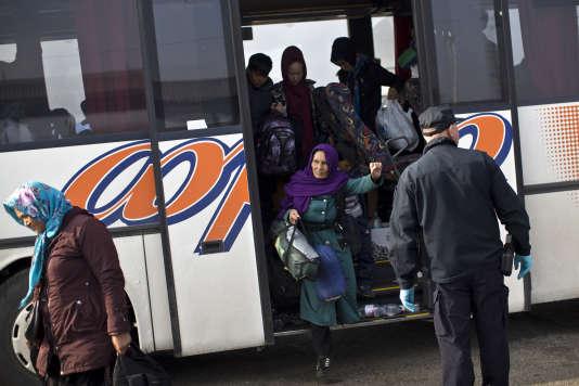 Des migrants descendent d'un bus arrivant de Serbie pour s'enregistrer dans le centre pour migrants d'Opatovac, du côté croate de la frontière, le 24 septembre.