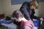 Une médecin bénévole examine un réfugié syrien à la base de loisirs de Cergy, jeudi 24 septembre.