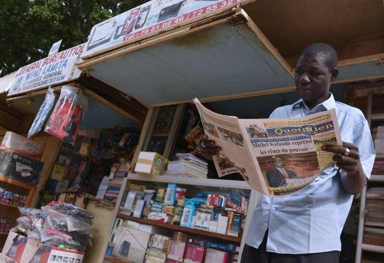 """Un homme lit un journal sur lequel on peut lire """"Michel Kafando reprend les rênes du pouvoir"""", le 25 septembre."""