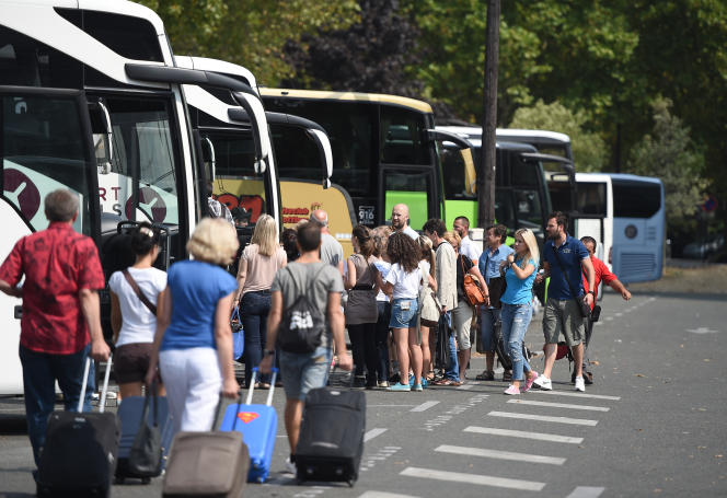 Des passagers à la gare routière de la Porte Maillot à Paris en août 2015.