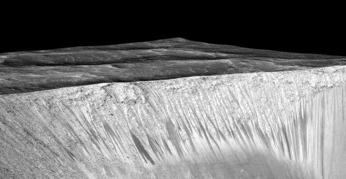 Les traînées sombres sur le flanc du cratère Garni sont attribuées à des coulées de saumure saisonnières.