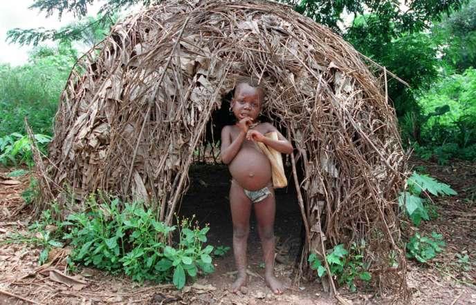 Un jeune Pygmée se tient devant une hutte, le 17 septembre 1999, dans la forêt équatoriale gabonaise.