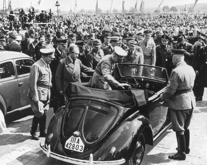 Adolf Hitler montant dans un des trois modèles de la nouvelle Volkswagen baptisée coccinelle par le Führer, derrière lui le Dr Porsche. Berlin, 1938.