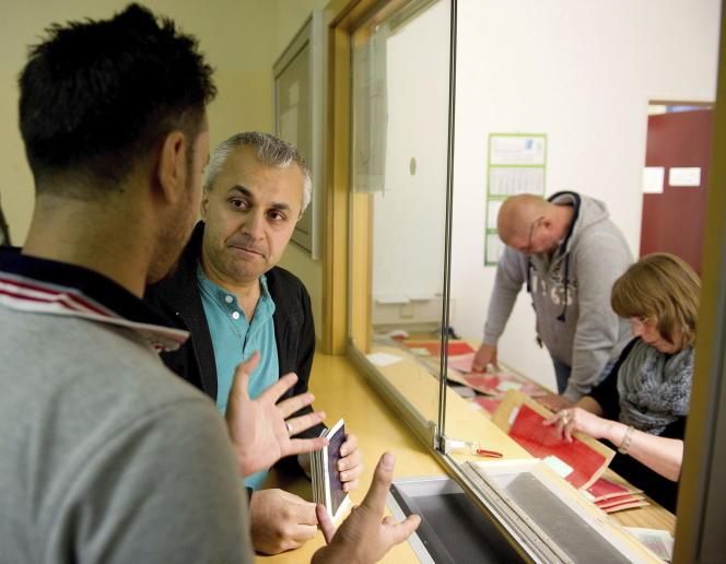 Un réfugié syrien est aidé par un traducteur à l'accueil du centre de réfugiés de Friedland en Allemagne, le 11 septembre.