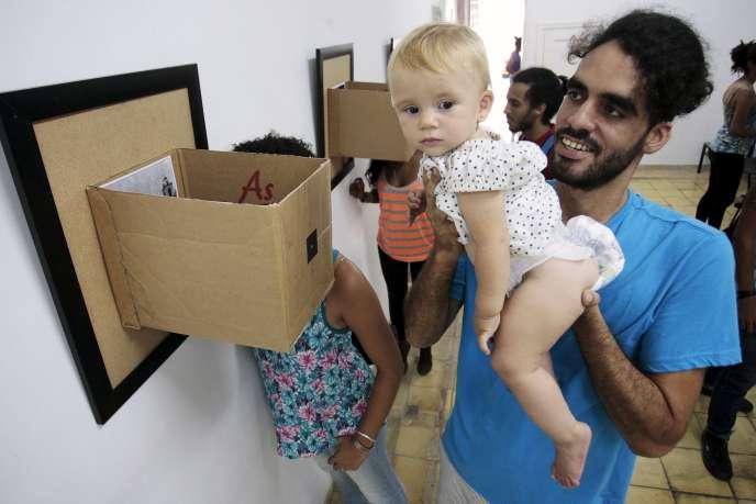 Le graffeur cubain Danilo Maldonado soulève sa fille pendant une exposition photo à La Havane, le 29 avril 2014.