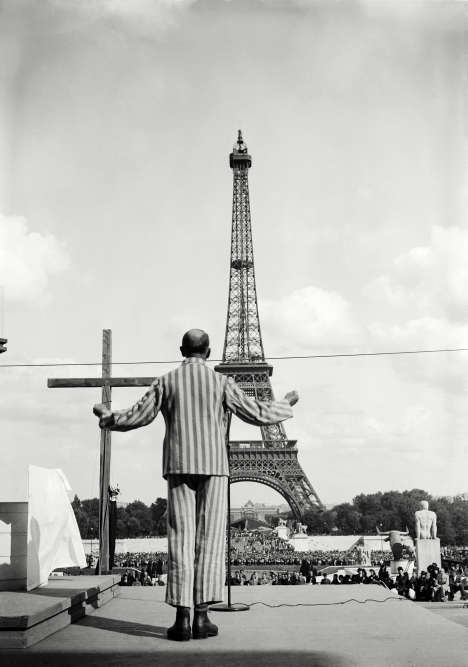 """""""Au premier regard, on ne peut être qu'être frappé par la puissance symbolique du maillage de verticales et d'horizontales de la tenue d'un déporté, la croix et la tour Eiffel dressée vers le ciel. Il s'agit de la représentation inédite d'un événement oublié : la messe organisée au Palais de Chaillot à l'été 1945 par une hiérarchie catholique à la réputation entachée par la compromission avec le régime de Vichy.   L'Eglise déploie son savoir-faire cérémoniel dans ce lieu profane. Exercice difficile, exercice ambigu car elle se refuse à tout mea culpa. Vu ici de dos, le révérend-père Michel Riquet a été opportunément chargé de prononcer une homélie. Résistant déporté, survivant de Mauthausen et de Dachau, il deviendra un grand prédicateur de l'après-guerre."""""""