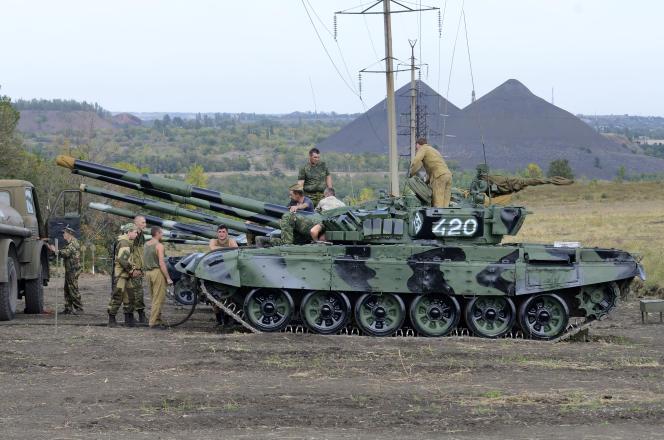 Des séparatistes soutenus par la Russie font le plein de carburant pour leur tank, fin septembre, dans la province de Donetsk, dans l'est de l'Ukraine.