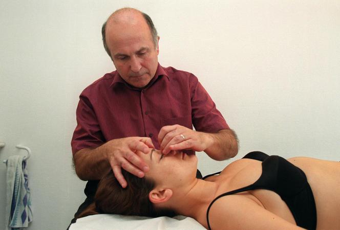 un ostéopathe exerce une pression sur des points du corps d'une patiente, le 17 octobre 2001 à Paris, pour essayer de réduire ses tensions musculaires.