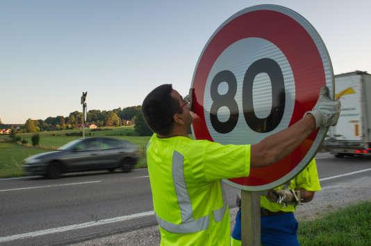 Mise en place d'un panneau de limitation de vitesse, sur la RN 57, à Hyet (Haute-Saône), le 1erjuillet 2015.
