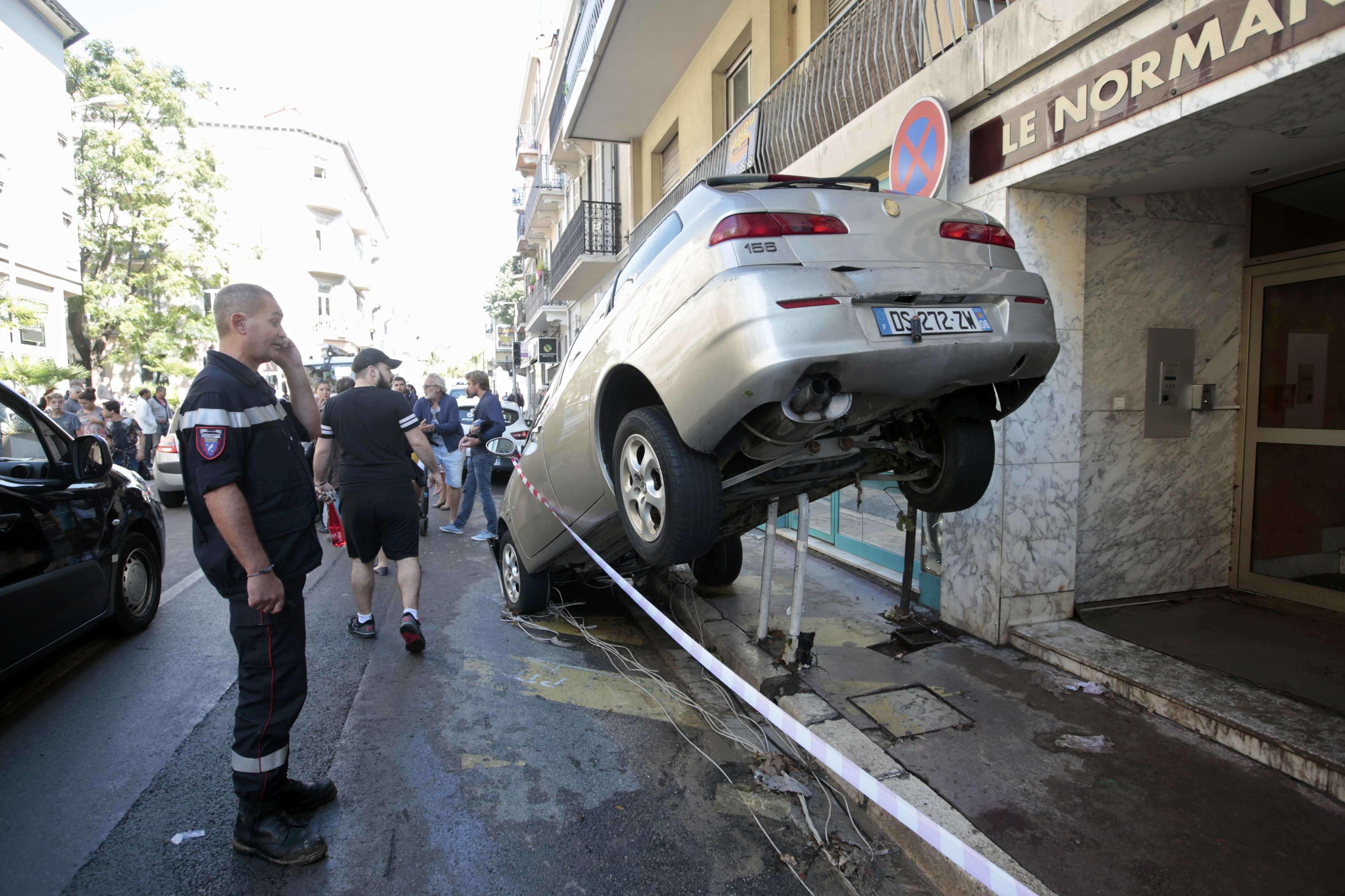 Voitures renversées, enchevêtrées, arbres arrachés, routes barrées. Dimanche 4octobre, un pompier de Cannes établit un cordon de sécurité à côté d'une voiture emportée par les pluies torrentielles dans la nuit du 3 octobre 2015.
