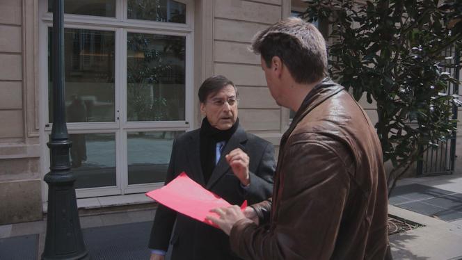 Devant le siège du Crédit mutuel à Paris, Alain Fradin, directeur général de la banque, a du mal à répondre aux questions que lui pose le journaliste Nicolas Vescovacci.