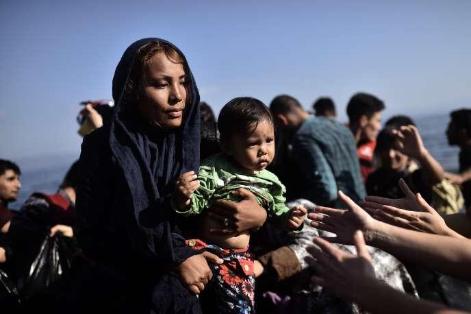 Une femme tient son enfant en arrivant à Lesbos, en Grèce, après avoir traversé la mer Egée.