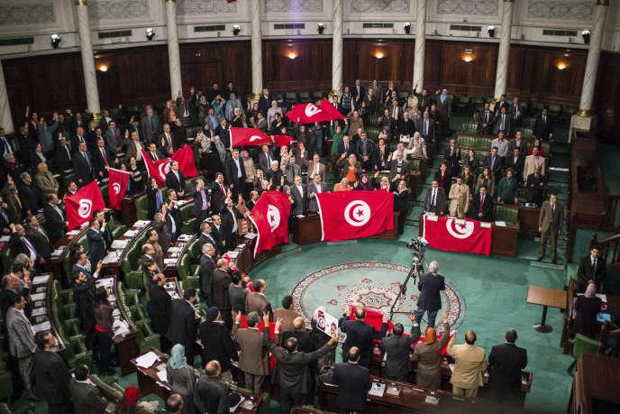 Les membres de l'Assemblée constituante tunisienne célèbre l'adoption de la nouvelle constitution, à Tunis, le 26 janvier 2014.