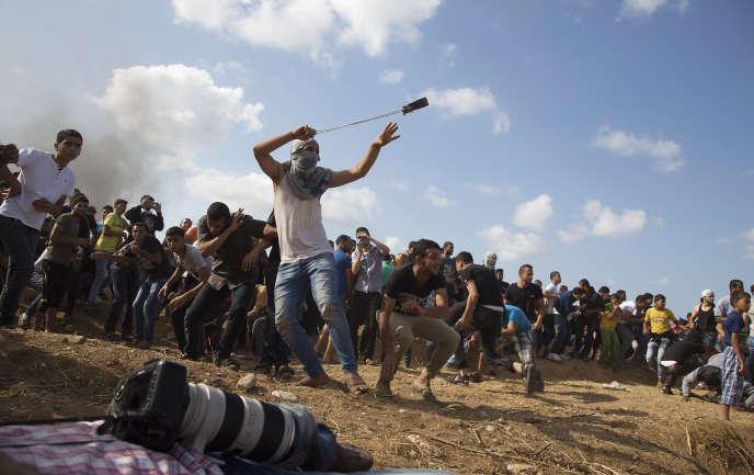 Un Palestinien lance une pierre sur des soldats israéliens à la frontière de la bande de Gaza, le 9 octobre.