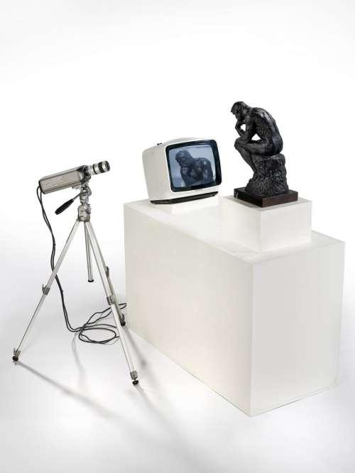 """« L'artiste coréen Nam June Paik, pionnier de l'art vidéo, met en scène une petite version du """"Penseur"""" de Rodin, installé face à un moniteur sur lequel se révèle, en direct, sa propre image, dans une boucle vidéo qui annonce l'ère électromagnétique des échanges des subjectivités au sein du """"village global"""". """"Le Penseur"""", passé au crible des télétechnologies. »"""