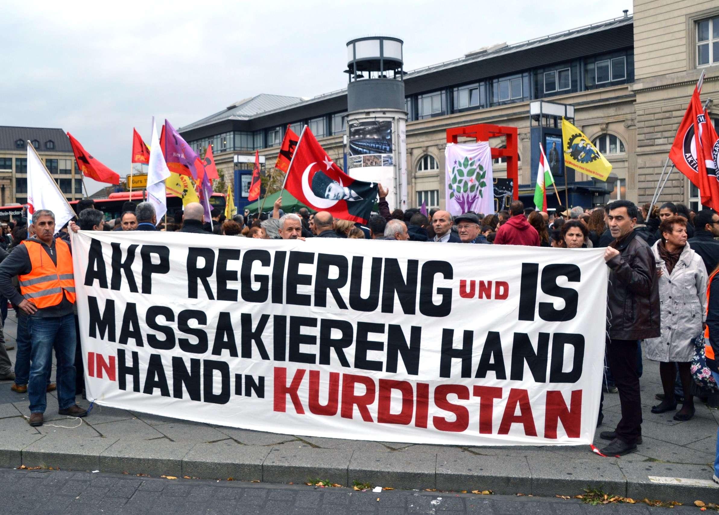 """Une bannière est brandie par des manifestants à Mannheim, en Allemagne. """"Le gouvernement de l'AKP et l'Etat islamique massacrent le Kurdistan main dans la main"""" peut-on y lire."""