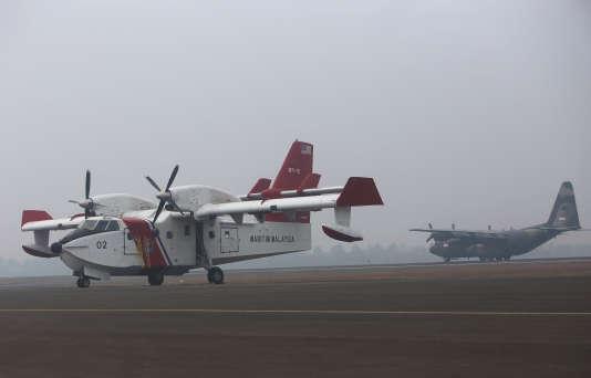 Un avion Bombardier de Malaisie et un hélicoptère Chinook de Singapour arrivent  sur la base militaire de Palembang, en Indonésie, le samedi 10 octobre. Ils commenceront sous peu à arroser les zones affectées.