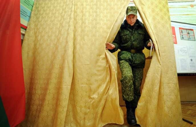 Un militaire biélorusse sort d'un isoloir lors d'élections anticipées mercredi 7 octobre à Minsk.