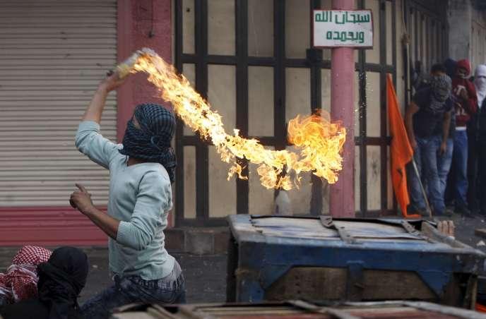 Un manifestant palestinien lance un cocktail molotov sur les soldats israéliens lors d'affrontements dans la ville d'Hébron en Cisjordanie, le 10 octobre