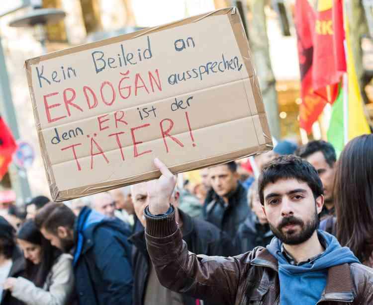 """Un homme porte une pancarte sur laquelle est inscrite l'inscription """"Pas de condoléances pour Erdogan, c'est lui le coupable"""" lors d'un rassembleement à Hambourg, en Allemagne."""
