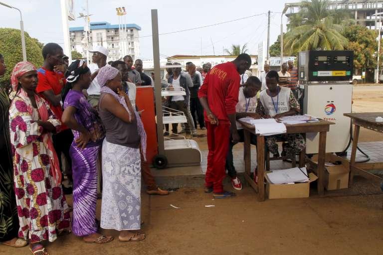 Les Guinéens ont voté massivement dimanche 11 octobre pour désigner leur président, un scrutin sous tension dont l'opposition compte déjà contester les résultats, alors que le camp du sortant Alpha Condé le donne vainqueur dès le premier tour. (Photo d'un bureau de vote installé dans une station essence à Conakry.)