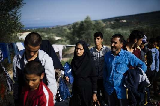 """Sur l'île de Lesbos en Grèce, des réfugiés font la queue pour être enregistrés au centre de Moria, transformé ce vendredi 16 octobre en """"hot spot"""" destiné à identifier les réfugiés susceptibles de recevoir l'asile politique en Europe."""