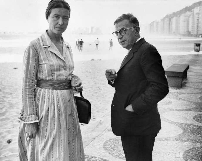 Les écrivains et philosophes français, Simone de Beauvoir et Jean-Paul Sartre se promènent sur la plage de Copacabana à Rio, le 21 septembre 1960.