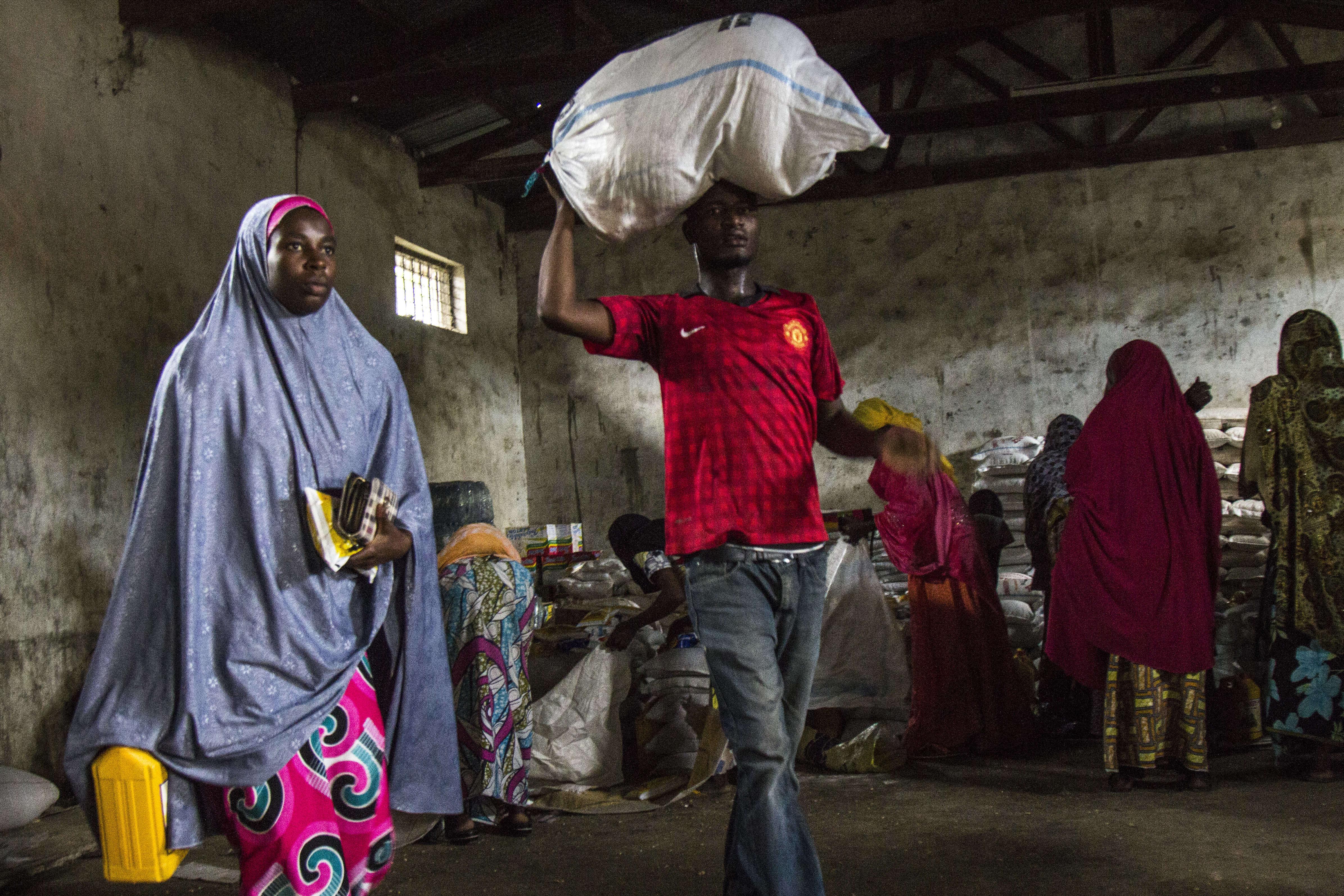 Centre de distribution du CICR à Maiduguri. Depuis le début du conflit, un nombre croissant de veuves mendient dans les rues. Elles comptent parmi les plus vulnérables. Grâce au soutien de plusieurs acteurs humanitaires, comme le CICR, elles reçoivent une aide alimentaire durant six mois et un soutien pour créer leurs microprojets générateurs de revenus.