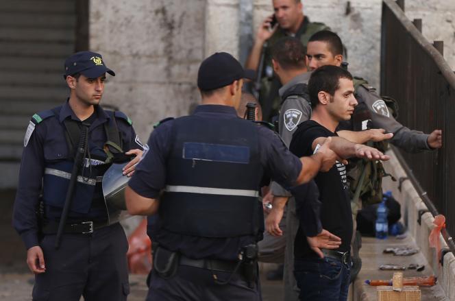 Des policiers israéliens contrôlent un Palestinien à l'entrée de la vieille ville de Jérusalem-Est, le 13 octobre 2015.