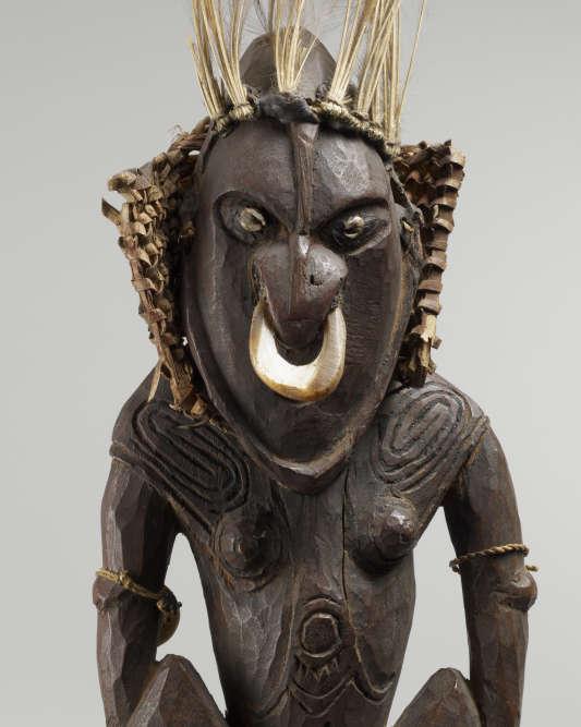 Cette statuette en bois porte le masque qui cache le visage des femmes dansant pour la cérémonie du début de la ménopause. La coiffure du masque en plumes, les motifs gravés sur les clavicules et les omoplates représentent la partie masculine ; le cercle lunaire autour du nombril évoque le monde féminin.