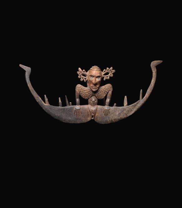 Crochet et figure féminine : les oreilles – démesurément grandes – sont habilement ajourées. Les motifs sculptés sur le buste révèlent des scarifications. Cette sculpture – qui provient de la vallée du moyen Sepik – aurait servi pour présenter des crânes humains.